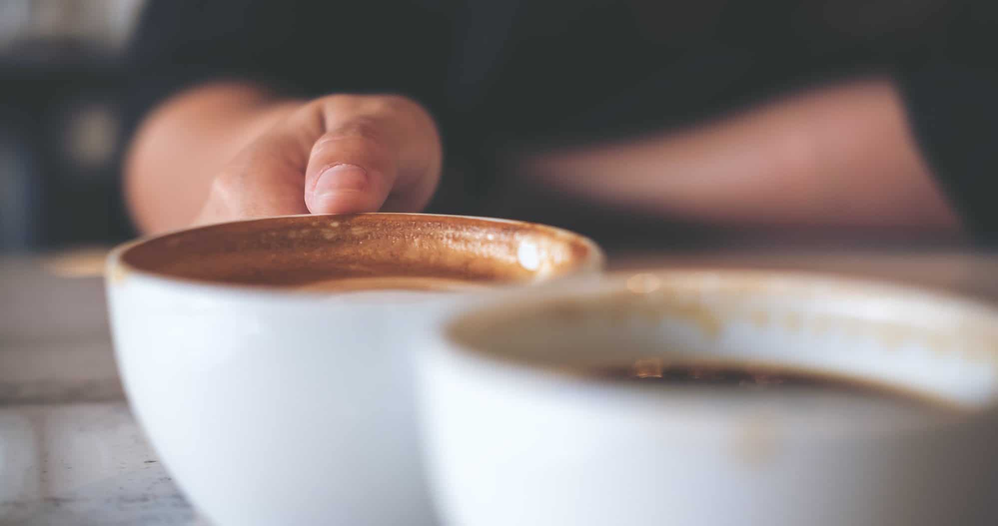 This is a picture of a Close up image of two people clink white coffee mugs on wooden table in cafe for an article called Competitive Intelligence elicitation techniques by Octopus Competitive Intelligence resolving your problems with Market Analysis & Competitor Analysis