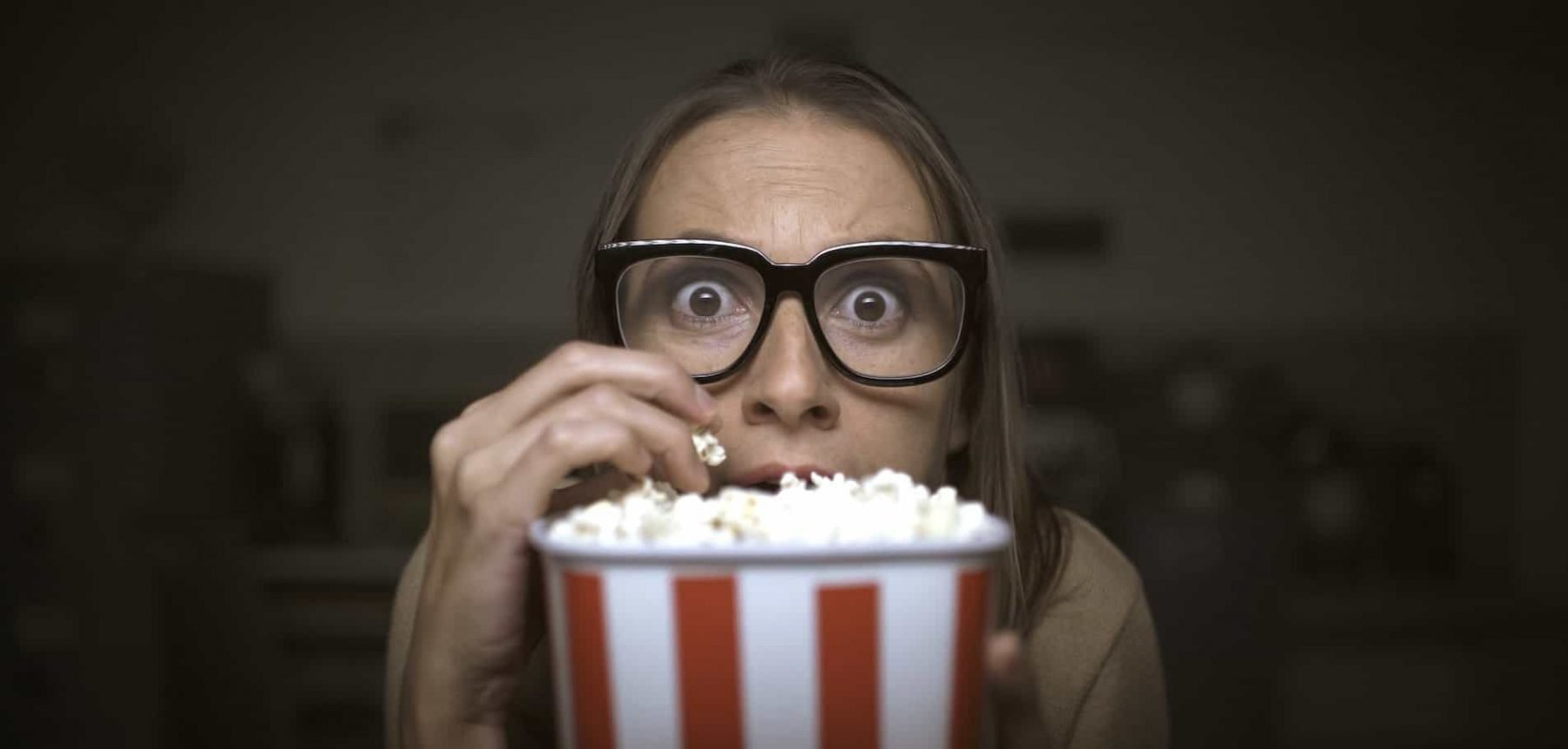 This is a picture of funny scared woman watching horror movies and eating popcorn at home for an article called Why Competitive Intelligence can help any size company by Octopus Competitive Intelligence who answer the questions when you just need to know