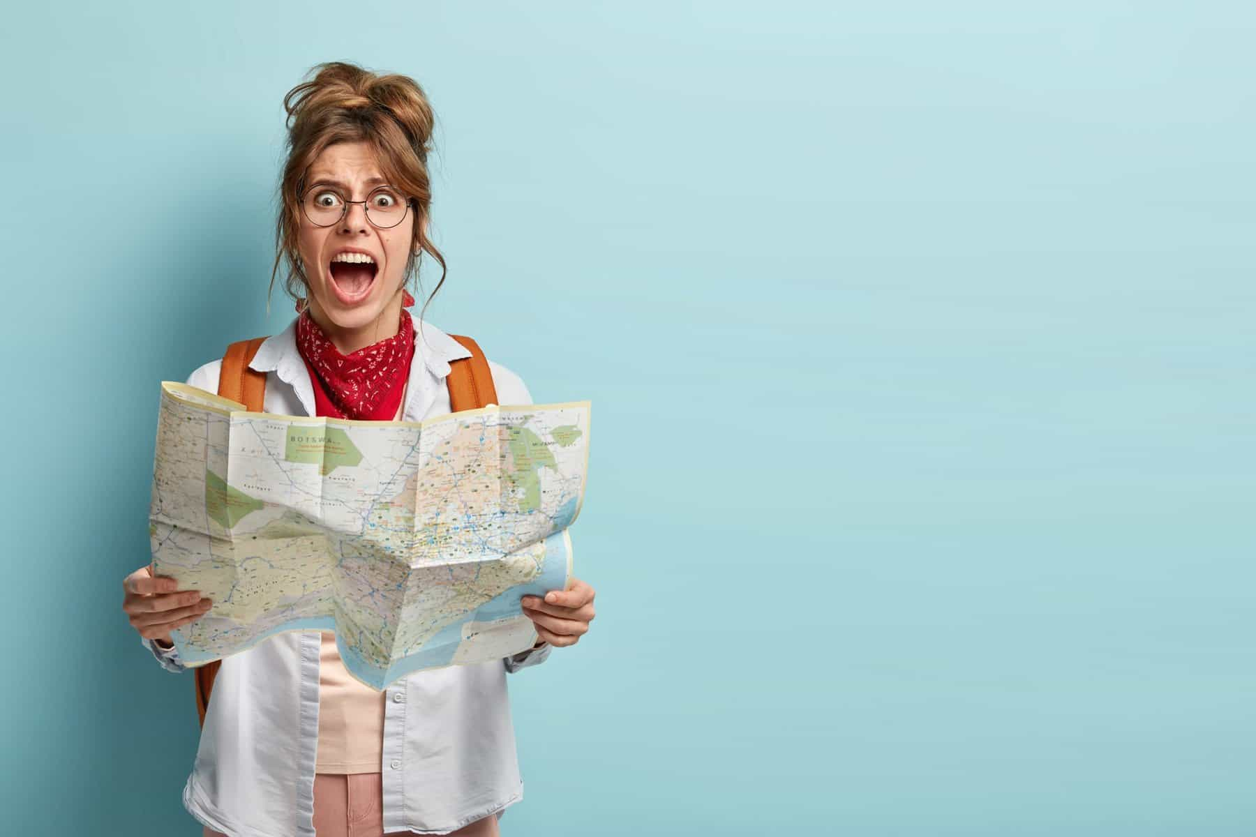 This is a photo of frustrated woman traveler lost in city, looks depressed at paper map, shouts from despair, has tour on vacation, carries backpack, wears big round spectacles for an article entitled What is win-loss analysis and how to do it? by Octopus Competitive Intelligence beat competitors, increase sales, solve problems, Competitor Analysis