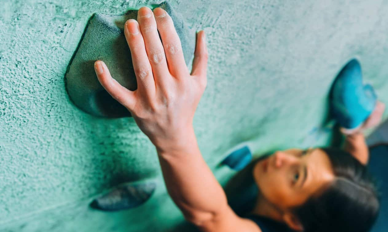 This is a picture of a Woman climbing up on wall in gym for an article called The Complete Guide to Market Analysis by Octopus Competitive Intelligence beat competitors, increase sales, reduce risk, solve problems, Competitor Analysis