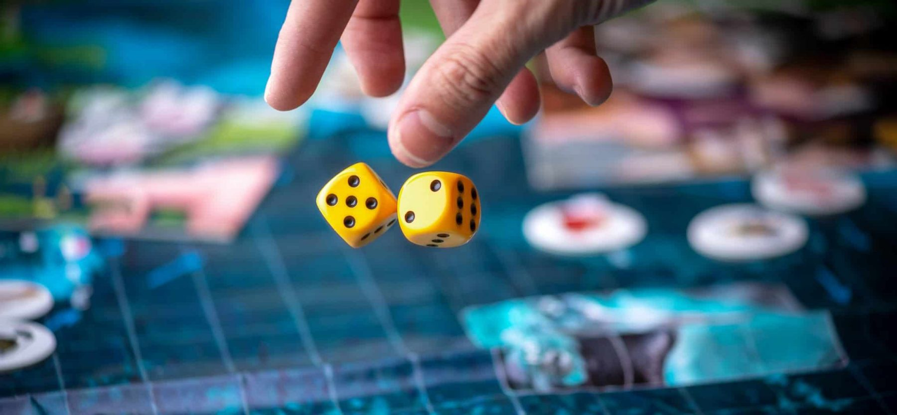 This is a picture of a hand throws two yellow dice on the blue field of the fantasy game Board games strategy for an article called the benefits of Win Loss Analysis, by Octopus Competitive Intelligence strategic intelligence due diligence and Market analysis