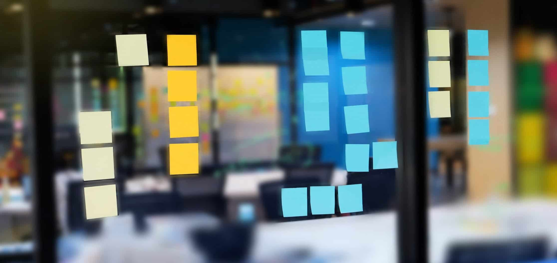 This is a picture of a Colourful post it on glass wall at meeting room with marker and sticky notes for people share ideas for an article called Head of Competitive Intelligence answers the questions by Octopus Intelligence and Corporate Investigations get in touch no obligation chat