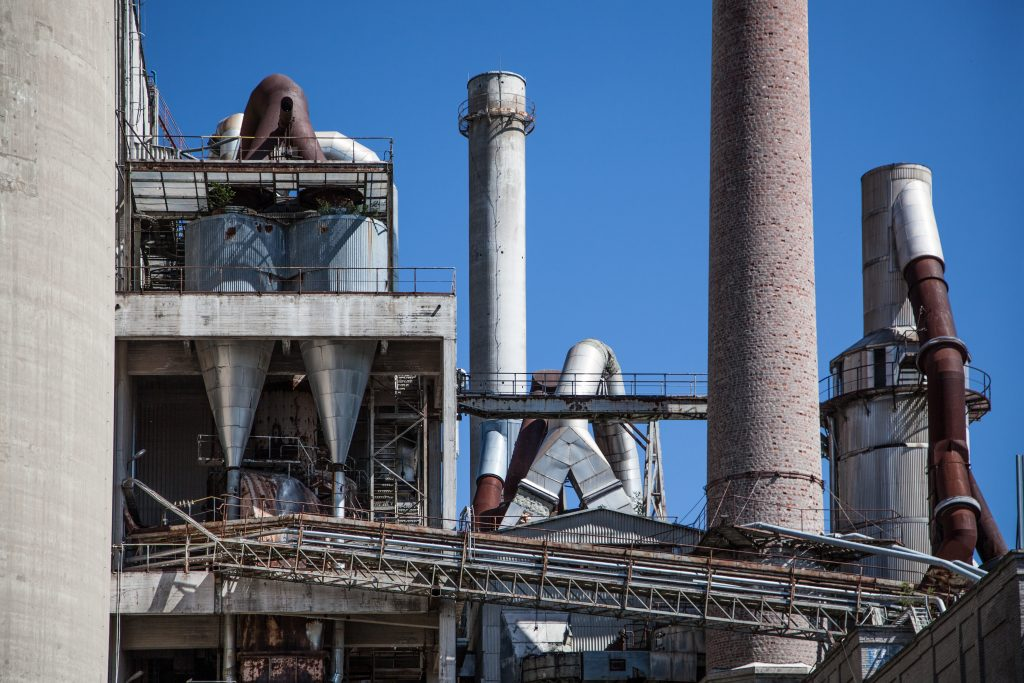 This is picture of a factory with two chimneys and hoppers for an article called HowCompetitive Intelligence increased the understanding of competitor production levels by Octopus Competitive Intelligence, Market Intelligence Competitor Analysis get in touch no obligation chat