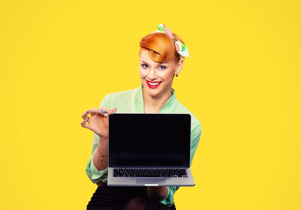 This is a picture of Girl with laptop green button shirt holding pc computer smiling looking at you camera retro vintage hairstyle for an article called Octopus Intelligence announce a complete rebuild of their website by Octopus is a Competitive Intelligence Competitor Analysis & Strategy consulting firm focused on creating certainty insight competitive advantage & significant growth