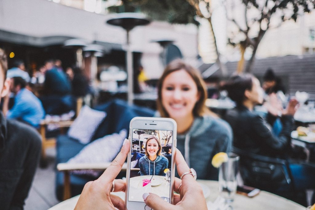 This is a picture of a girl having a photo taken for a social media post for a case study called Social Media subscriber Competitor Analysis and Win-Loss Analysis Case Study by Octopus is a Competitive Intelligence Competitor Analysis focused on creating certainty