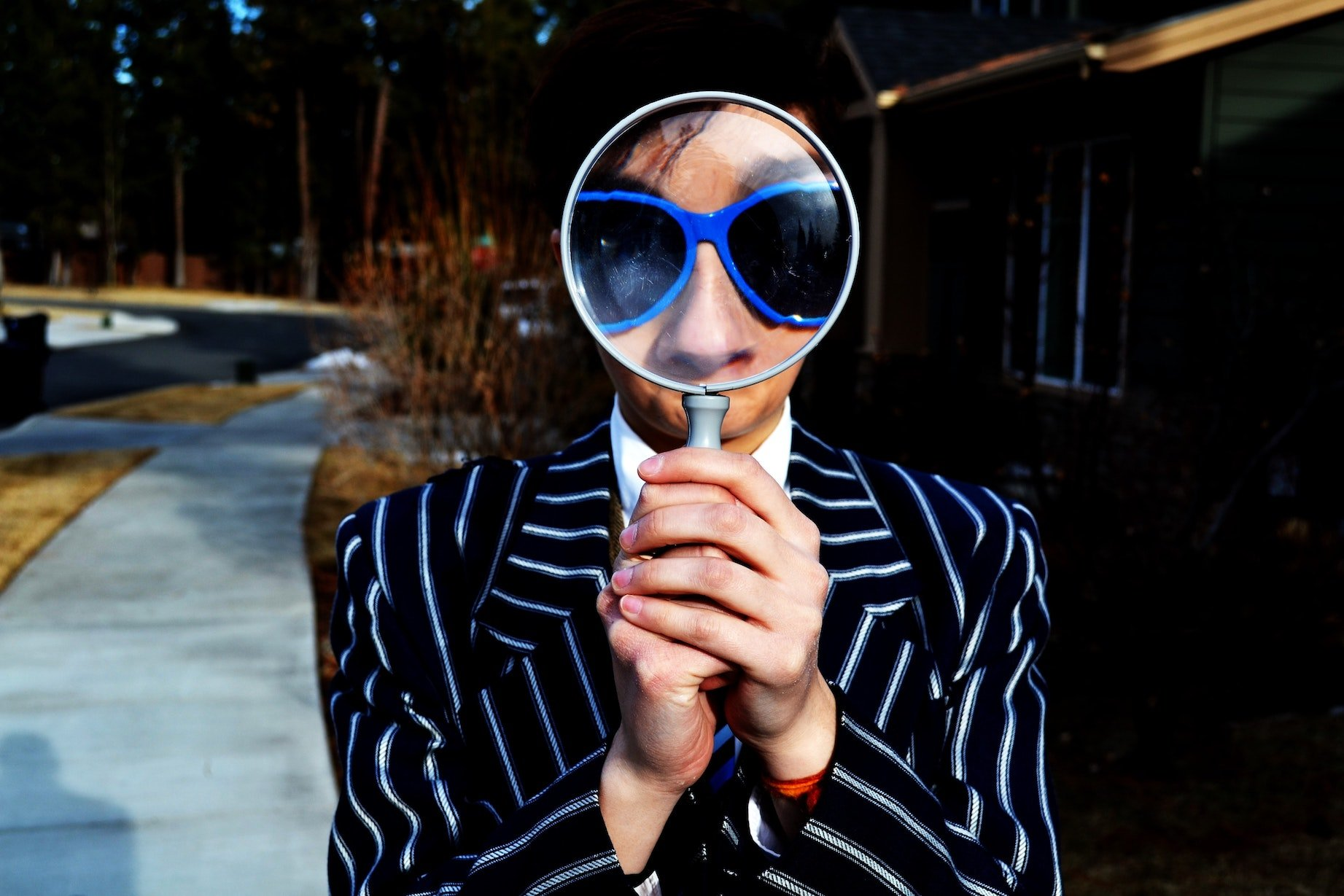 This is a picture a well dressed man looking through a magnifying glass for an article called Competitive Analysis to Find Out Who Your Competitors Are by Octopus Competitive Intelligence Competitor Analysis focused on creating certainty